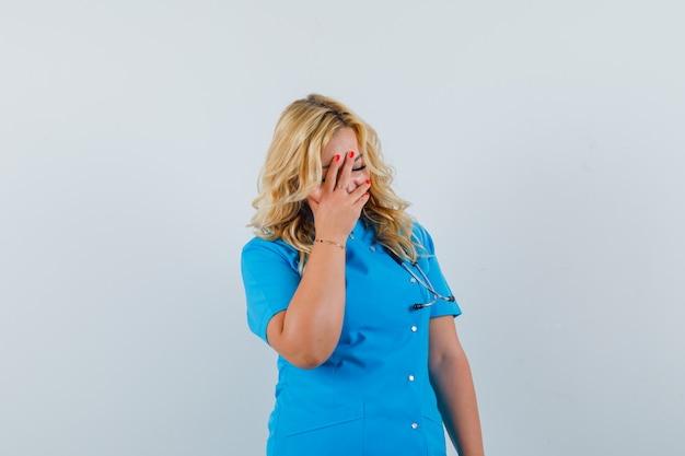 Medico femminile che tiene la mano sul suo viso in uniforme blu e sembra annoiato