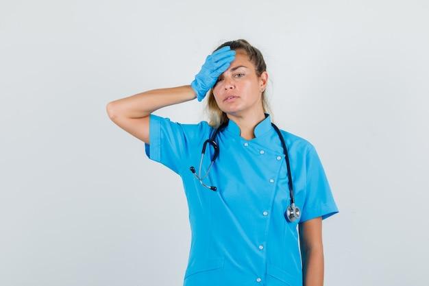 Женщина-врач, держащая руку на лбу в синей форме