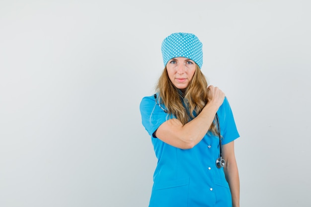 파란색 유니폼에 어깨 통증에 손을 잡고 여성 의사