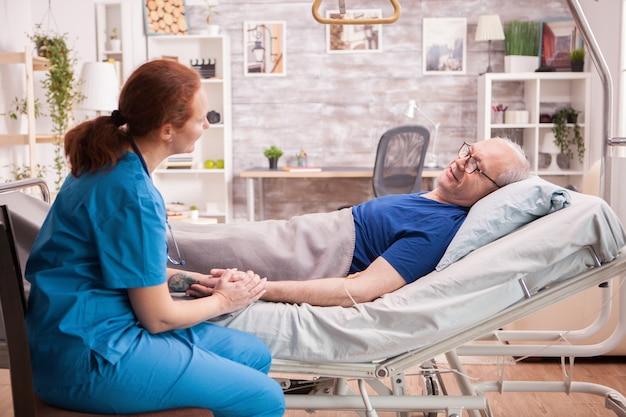 Female doctor holding hand of senior man in nursing home bed.