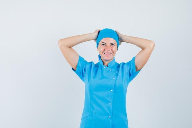 青い制服を着て頭の後ろで手をつないで、うれしそうに見える女医。正面図。
