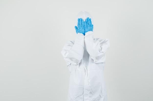 Medico femminile che tiene le mani sul viso in tuta protettiva