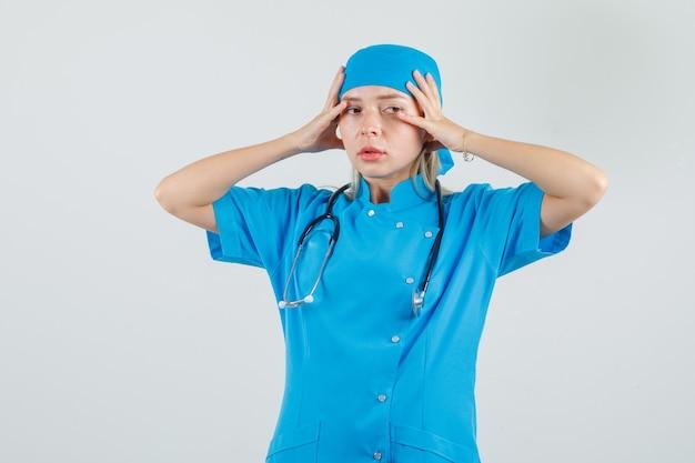 Medico femminile che tiene le mani alla testa in uniforme blu e che sembra infastidito