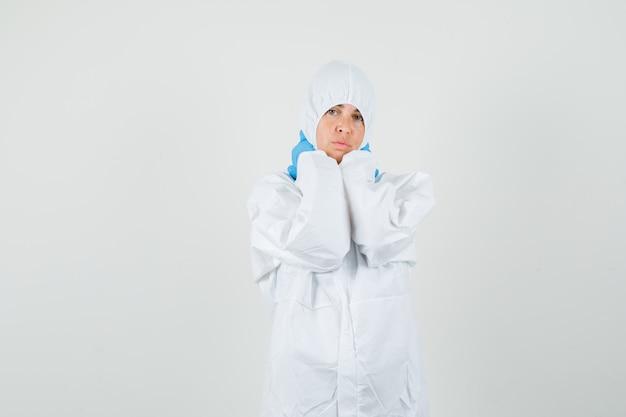 Medico donna che tiene le mani sul collo in tuta protettiva