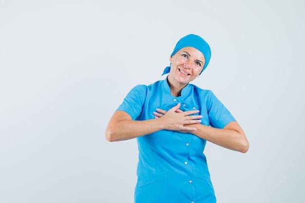 青い制服を着て胸に手をつないで感謝している女医。正面図。