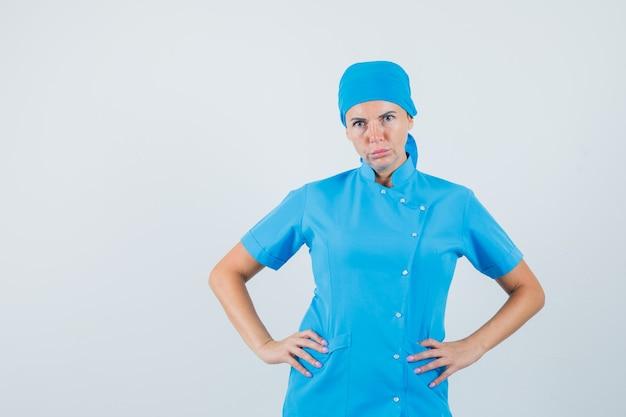 青い制服を着て腰に手をつないで真面目な女性医師、正面図。