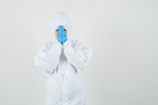 Medico femminile che tiene le mani nel gesto di preghiera in tuta protettiva