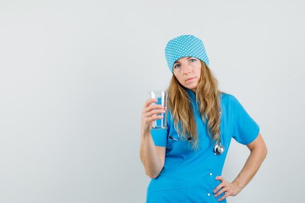 青い制服を着た計量カップを保持している女性医師