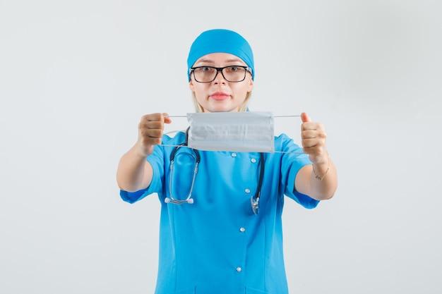 青い制服を着た医療マスクを保持している女性医師
