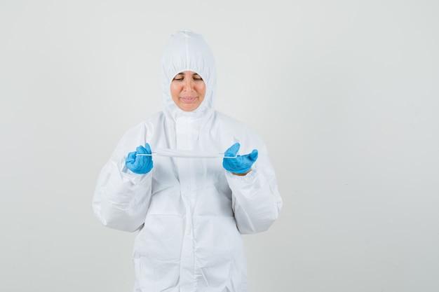 Medico femminile che tiene mascherina medica in tuta di protezione