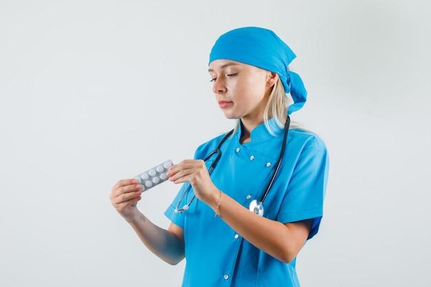 青い制服を着た錠剤のパックを保持している女性医師