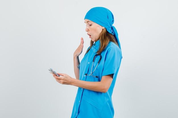 Женщина-врач держит упаковки таблеток в синей форме и выглядит удивленным.