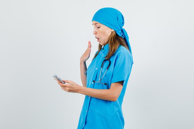 Medico femminile che tiene confezioni di pillole in uniforme blu e che sembra sorpreso.