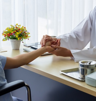 Female doctor holding patient's hand for encouragement and empathy and touching her arm.