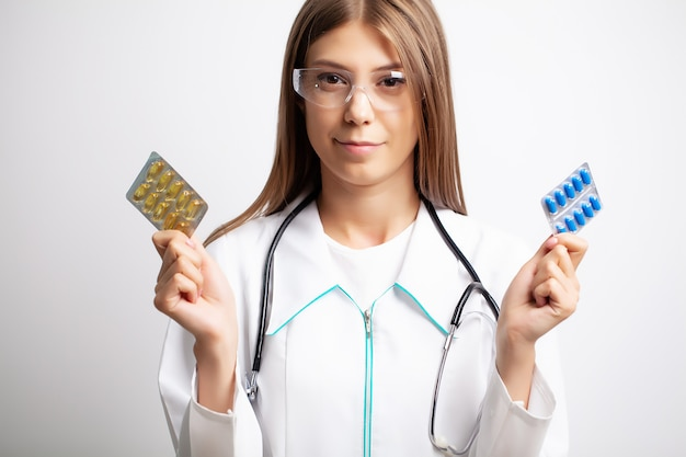 Женщина-врач держит таблетки в руках