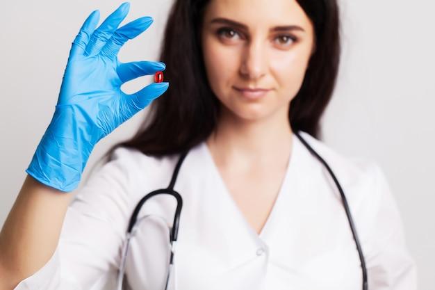 Женщина-врач держит таблетки, предписанные для лечения пациента