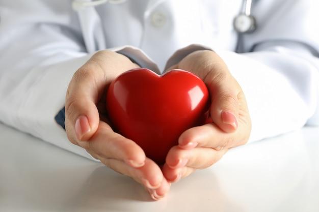 Женщина-врач держит красное сердце