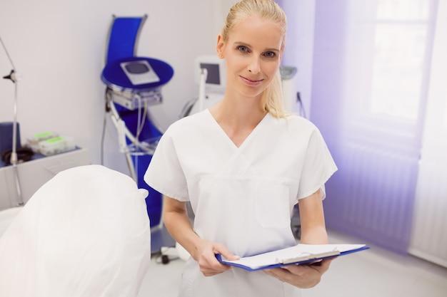 クリニックでレポートを保持している女性医師