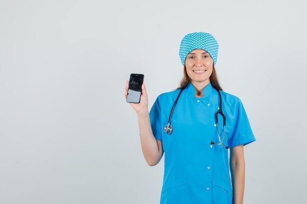 Женщина-врач держит смартфон в синей форме и выглядит весело