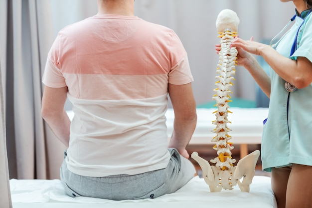 Female doctor holding spine model and pointing on vertebra while patient sitting on the hospital bed next to her with backs turned.