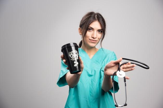 Женщина-врач, держащая стетоскоп и чашку кофе