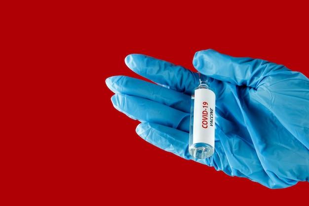 Женщина-врач держит шприц и вакцину covid-19, изолированную на красном. здравоохранение и медицинское понятие.