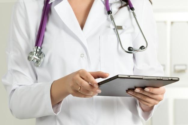 여성 의사 지주 태블릿 pc입니다. 의사의 손 클로즈업입니다. 의료 서비스 및 건강 관리 개념.