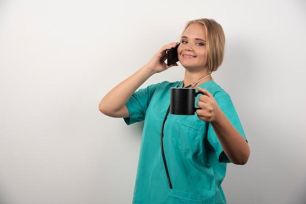 전화 통화 하는 동안 차를 들고 여성 의사입니다.