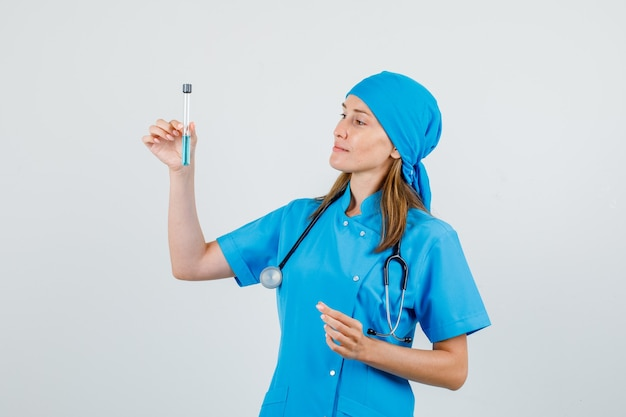 試験管を保持し、均一な正面図で笑顔の女性医師。