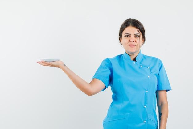 Medico femminile che tiene piattino bianco in uniforme blu e sembra sicuro