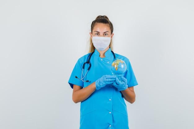 Medico femminile che tiene il globo del mondo in uniforme blu, maschera, guanti e guardando attento.