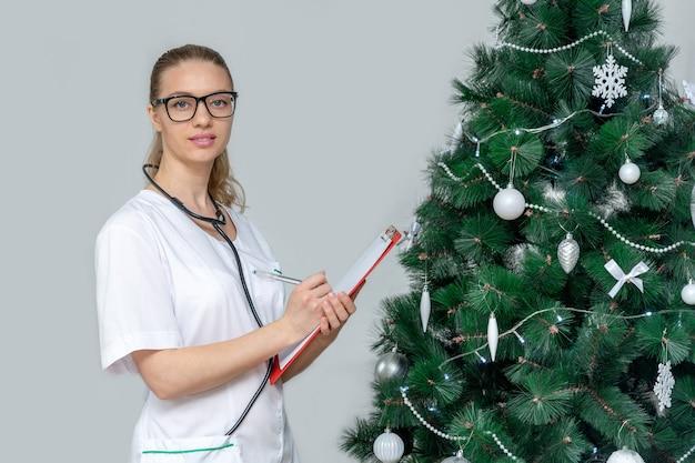 女性医師は、クリスマスツリーの背景にクリップボードを保持しています。病院で予約する