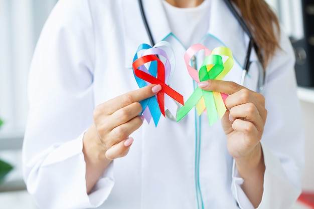 Female doctor holds colored ribbons symbolize awareness of various diseases.