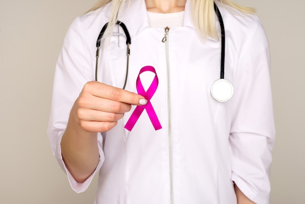 Female doctor holds pink ribbon, international breast cancer day october 7