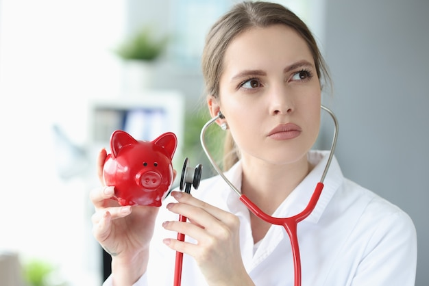 女医が赤いブタの貯金箱を持ち、聴診器をあてます
