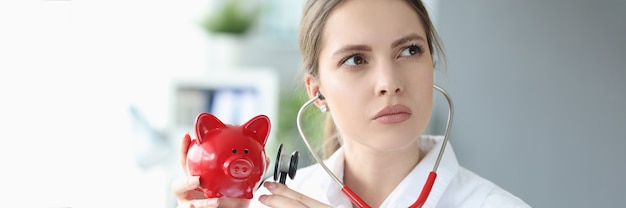 Female doctor holds red pig piggy bank and applies stethoscope to it