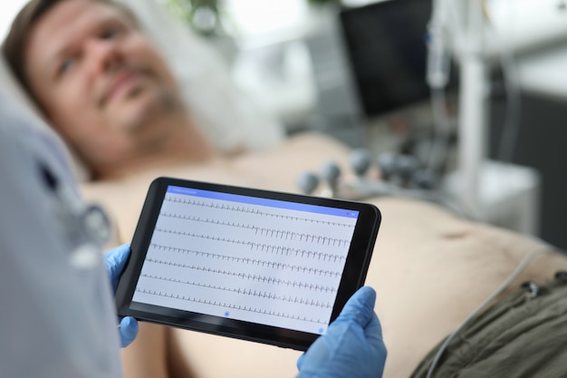 Female doctor holds tablet with electrocardiogram