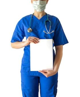 Женщина-врач в синей медицинской форме и маске держит чистый белый лист с копией пространства