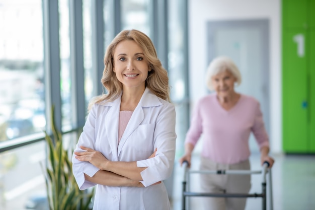 Женщина-врач в лабораторном халате стоит со скрещенными руками и улыбается