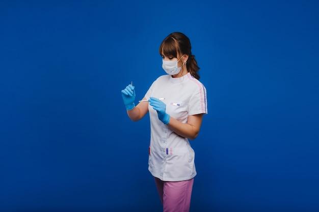 白い背景の上の診療所でピンセットを保持する方法を示すマスクと手袋の女性医師。医者は彼の仕事が幸せで大好きです。