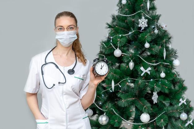 保護医療マスクの女性医師は、クリスマスの背景に目覚まし時計を保持します