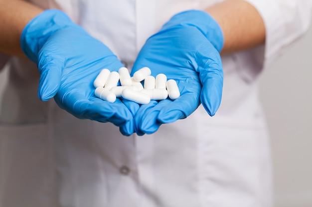 Женщина-врач в белом халате держит белые таблетки для похудения