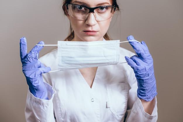 コロナウイルスからの保護のためにフェイスマスクまたは医療用マスクを示す白衣の女医