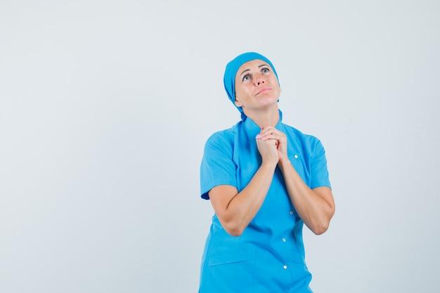 祈りのジェスチャーと希望に満ちた、正面図で手を握りしめる青い制服を着た女性医師。
