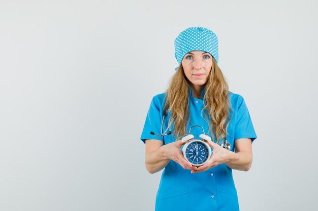 目覚まし時計を押しながら肯定的な青い制服を着た女医