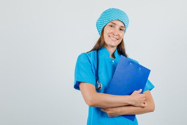 クリップボードを保持し、嬉しそうに見える青い制服を着た女医