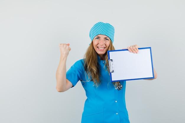 勝者のジェスチャーでクリップボードを押しながら幸せそうに見えて青い制服を着た女医