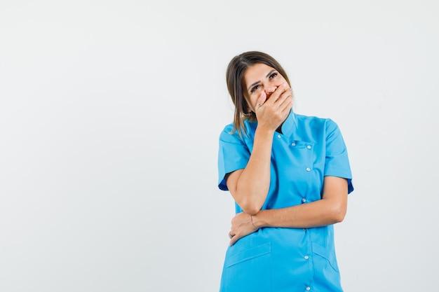 입에 손을 잡고 즐거운 찾고 파란색 제복을 입은 여성 의사