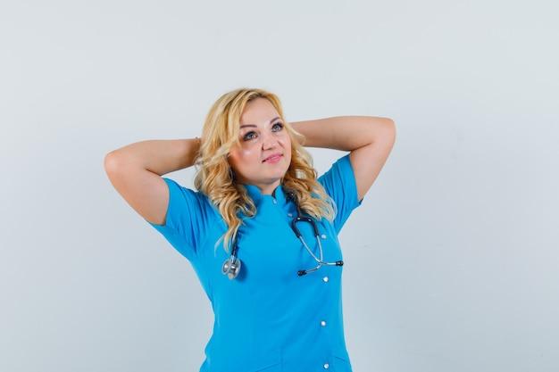 頭の後ろで手を握り、リラックスして見える青い制服を着た女性医師