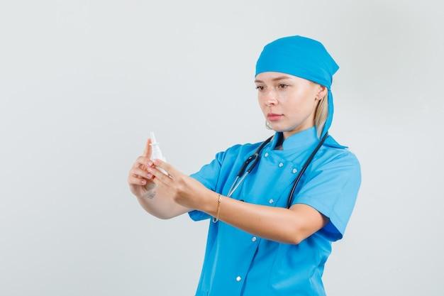 Женщина-врач в синей форме держит медицинскую бутылку